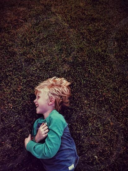 A little boy in the grass on an Autumn night.  photo