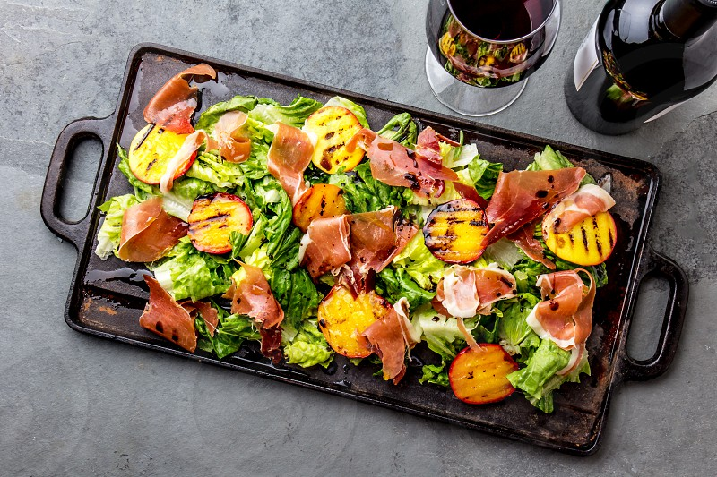 Lettuce ham serrano and grilled peaches salad served on black board with red wine. Top view. photo