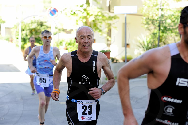man in black jersey with a number 23 on his waist running on the gray concrete road photo