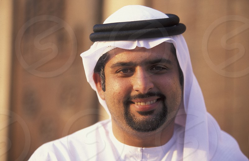 a portrait of a Arab men in the souq or Market in the old town in the city of Dubai in the Arab Emirates in the Gulf of Arabia. photo