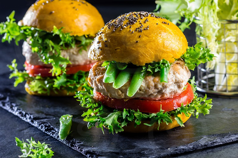 Colored yellow burgers. Homemade American chicken burgers hamburgers with turmeric curcuma and chia buns and vegetables. Trendy food. Close up slate background. photo