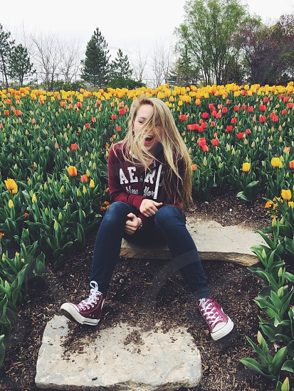 woman with long blonde hair wearing red aeropostable pull over hoodie and blue denim fitted jeans with red high top sneakers sitting on gray rock surrounded by red and yellow tulips during da photo