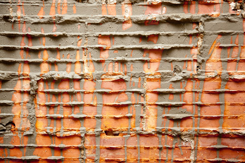 broken bricks in brickwall in wall construction with cement grout photo