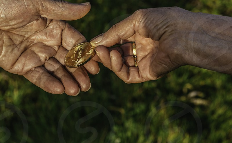 Senior woman hand is holding bitcoin coin giving to senior man hand on green nature background. Business Finance Investment and exchanging concepts photo