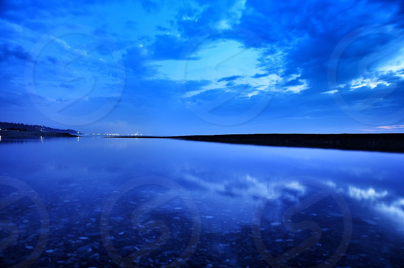 reflection of clouds on calm body of water photo