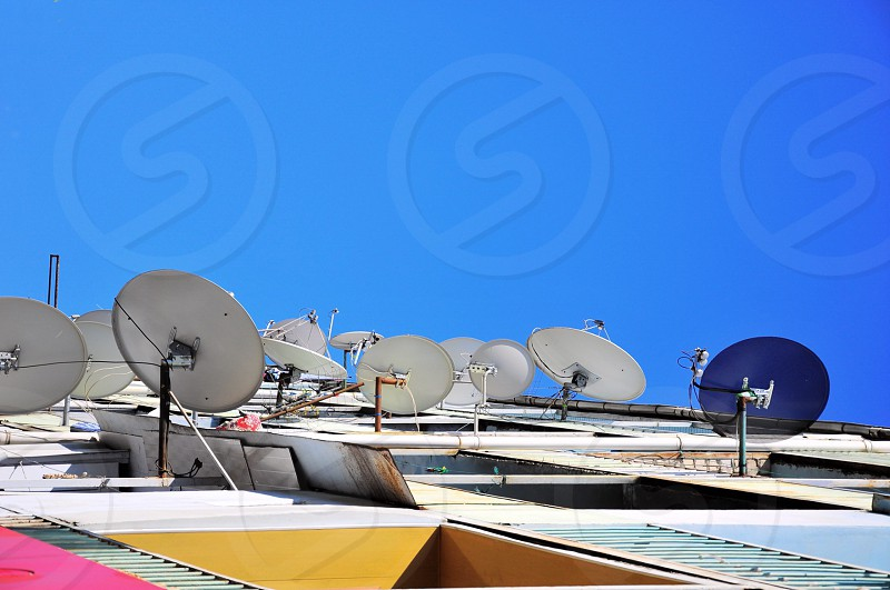 white and purple satellite dishes on yellow pink and green building under blue clear sky photo