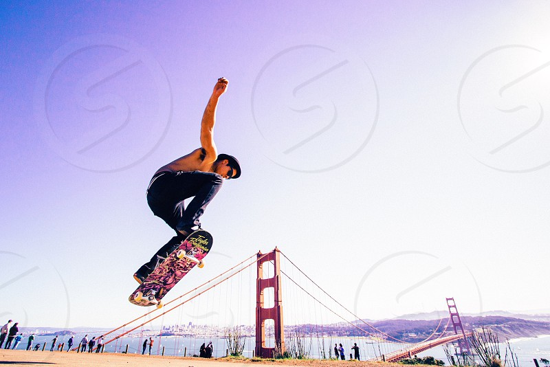 topless man doing stunts on skateboard with golden gate bridge view at distance during daytime photo
