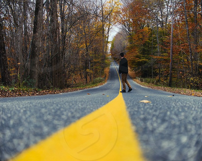man in black jacket and brown pants on yellow and gray winding road with green and yellow tress during day time photo
