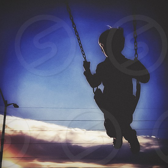 A boy on a swing at sunset in the summer.  photo