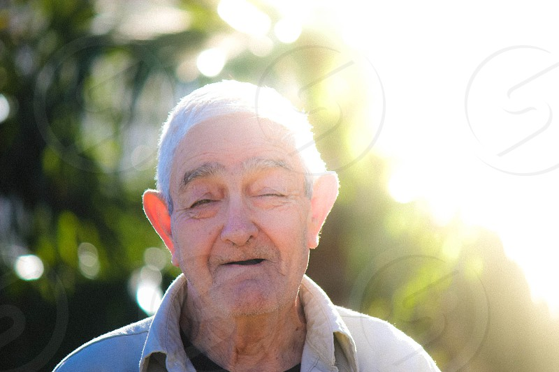 Elderly man smiling with sunshine behind him. photo