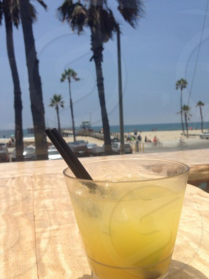 Beach cocktail overlooking palm trees and boardwalk. Blue skies photo