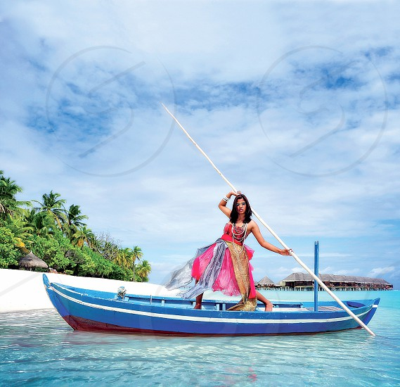 woman in pink dress on blue boat photo