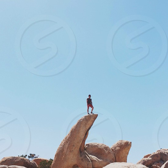 man in red shorts standing in the rock edge photo
