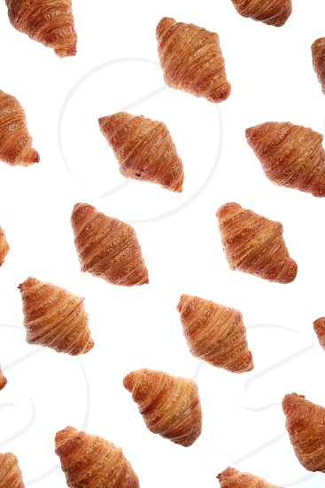 Food pattern with freshly baked homemade delicious croissants on a white background. photo