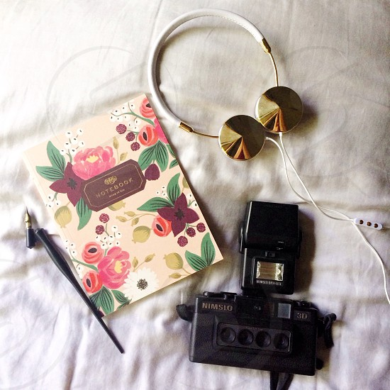 black camera near white cover with floral print photo