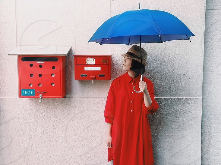 woman in red dress holding blue umbrella near mail boxes photo