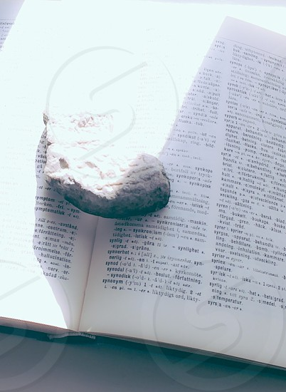 stone in the middle of an open book with daylight reflecting on book page photo