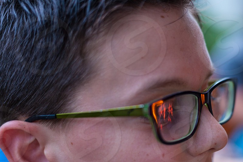 boy with green glasses. a campfire is reflected in his glasses. photo