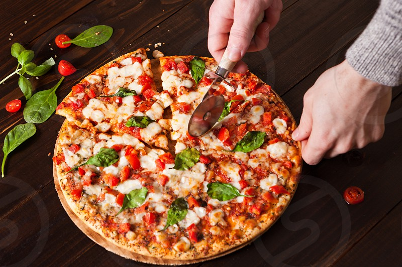 Overhead view of a margherita pizza on a dark wooden surface with Caucasian human hands photo