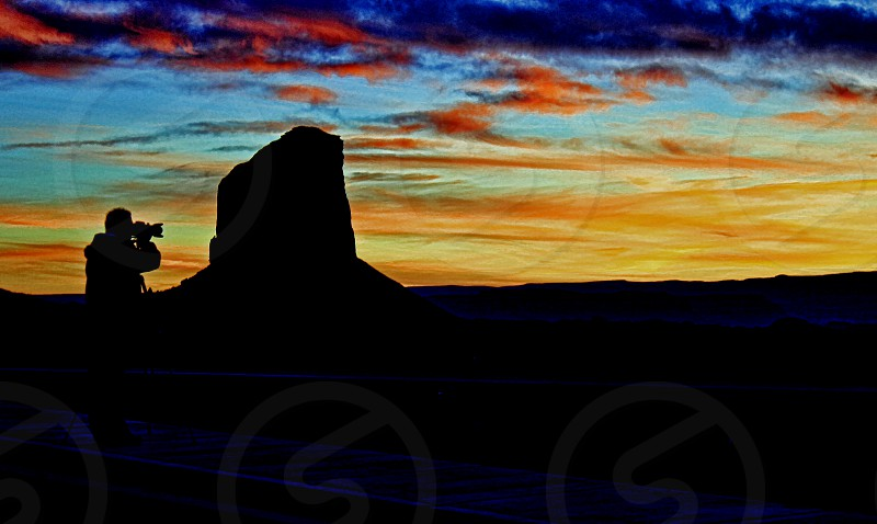 A photographer takes a picture of a rock formation as both are silhouetted against a orange and golden sunset photo