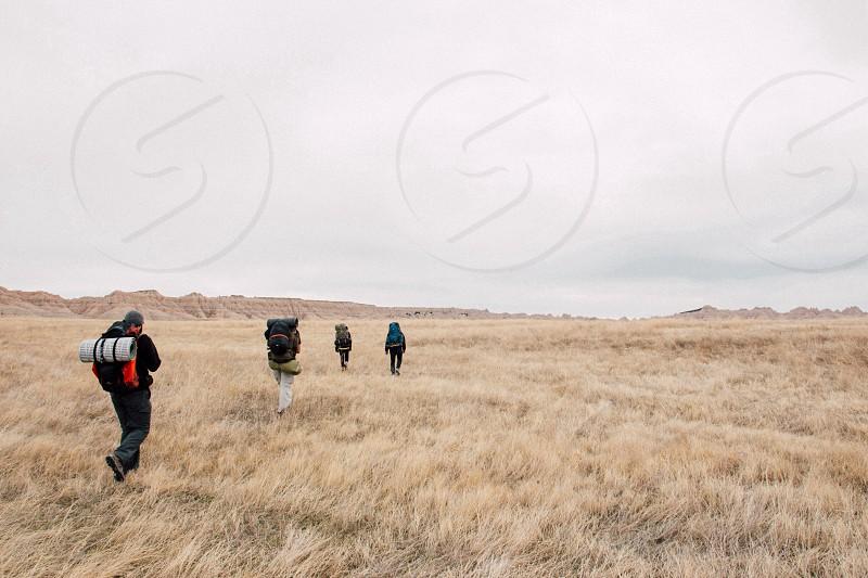 people hiking through brown grasses during daytime photo