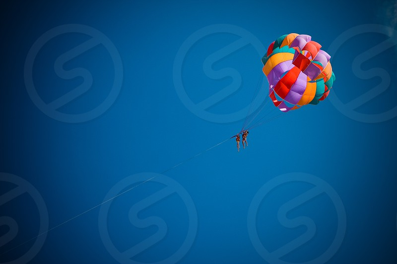 Two people ascending into a deep blue sky on a towed parachute. photo