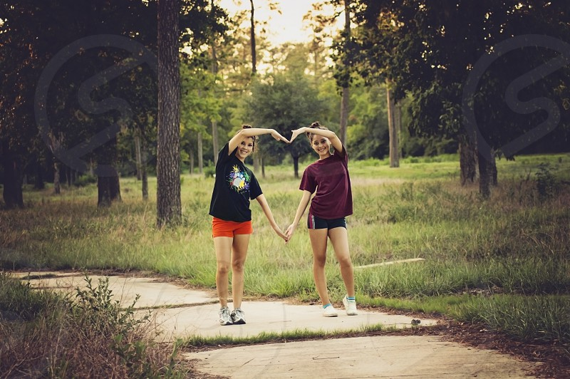Teenagers sisters or best friends creating a heart in a forest in Houston Texas USA photo
