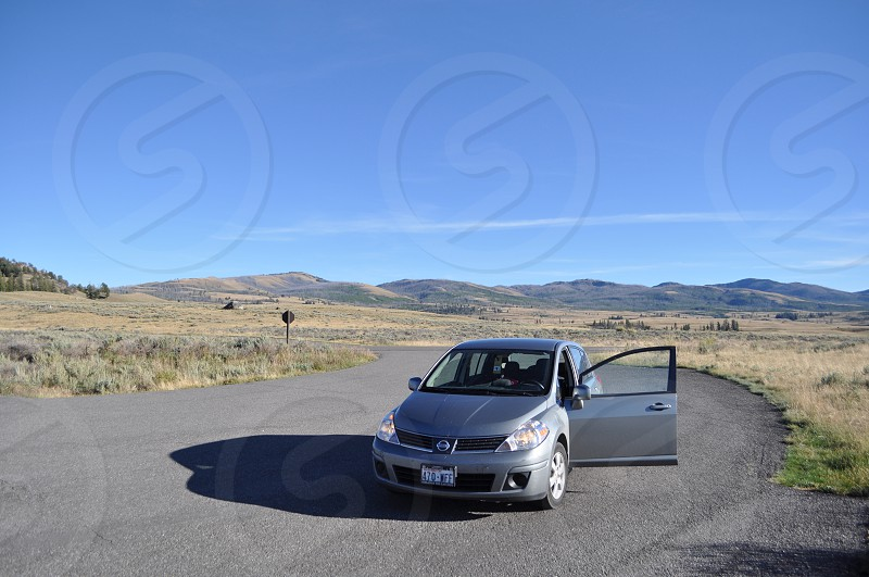 Little car in the middle of the roadtrip  Yellowstone plains photo