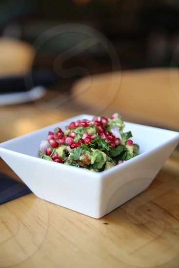 close up photo of red round beans and green sliced salad on white ceramic square saucer on brown wooden table photo