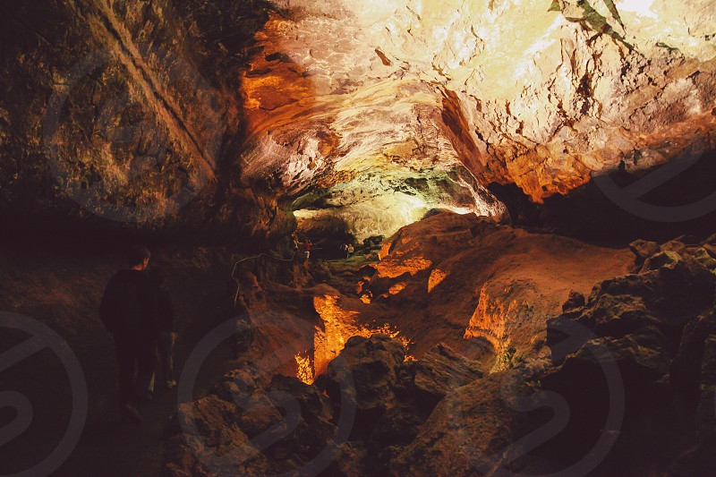 photo of two people walking inside a cave photo