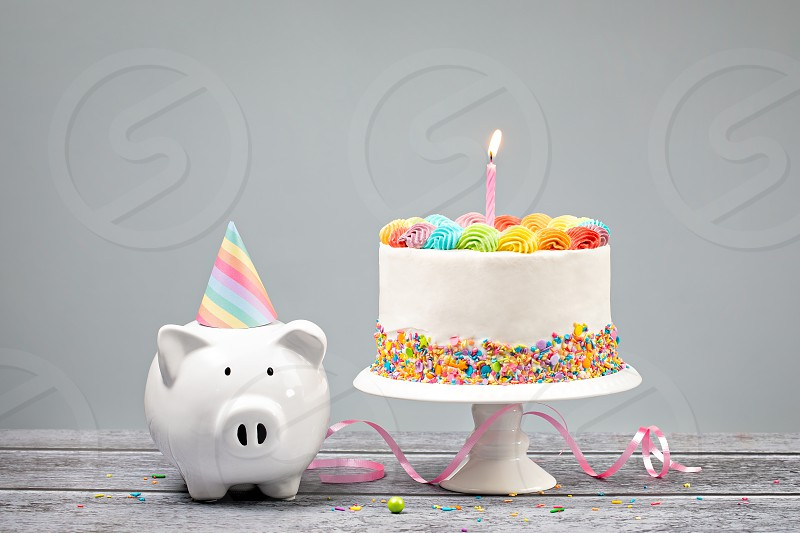 Birthday Money Concept with Rainbow Cake one Candle and cute Piggy Bank over a neutral background. photo