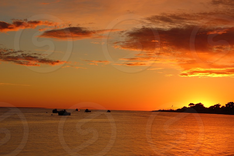dawn on the beach with fishing boats moored at sea and the sun rising on the horizon after the bay photo