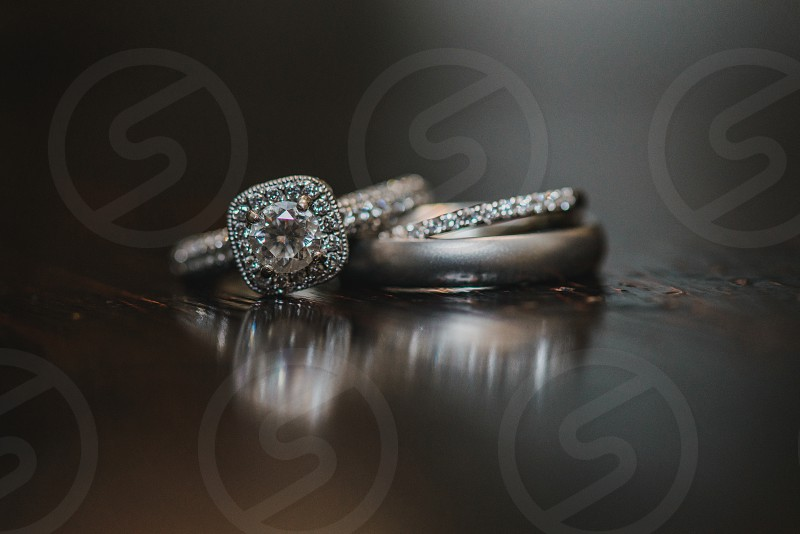 Silver wedding rings with diamonds on wood reflective surface photo