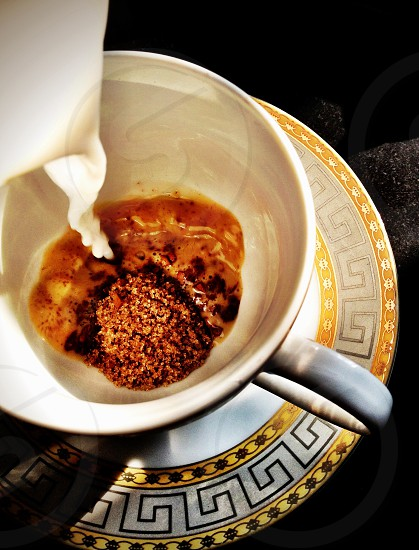 Adding milk in the cup to make delicious hot home made coffee photo