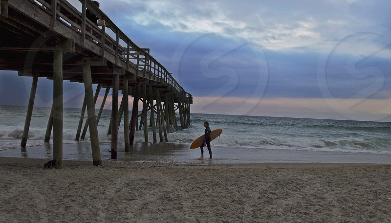 Lonely surfer leaving the beach due to a flat ocean. Walking near the pier and carrying his surf board.  photo
