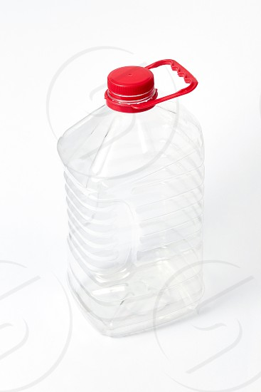 Transparent plastic big canister for water and other liquid with red cover on a light gray background with copy space. Mockup. photo