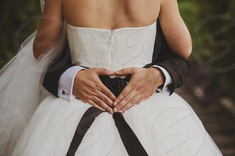 Bride and groom with heart in hands photo
