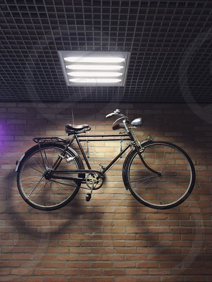 black bicycle hanging on the wall photo