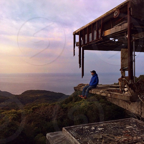 man in blue hoodie sitting on builidng cliff photo