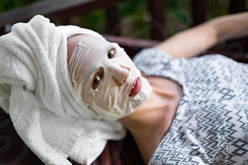 Woman in a disposable cosmetic mask on face photo