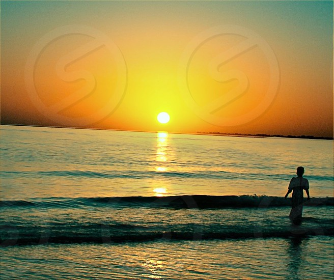 A Young girl in the ocean wearing a dress loving the Sunset.  photo