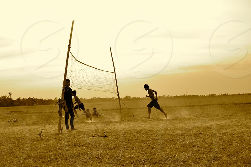children playing on brown field near volleyball net during golden hour photo