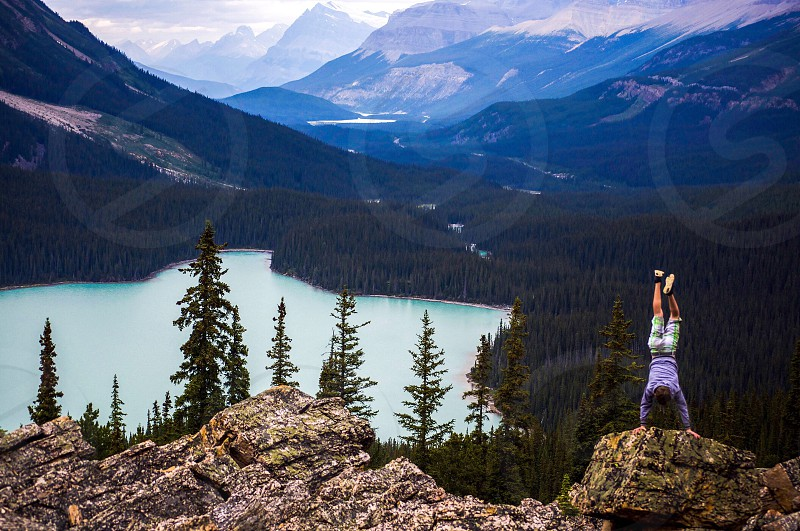person in purple jacket with white shorts doing hand stand on brown stone above mountain near trees and body of water photo