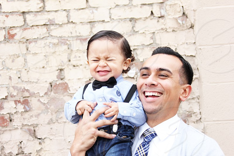 man holding up a boy wearing a bow tie smiling photo