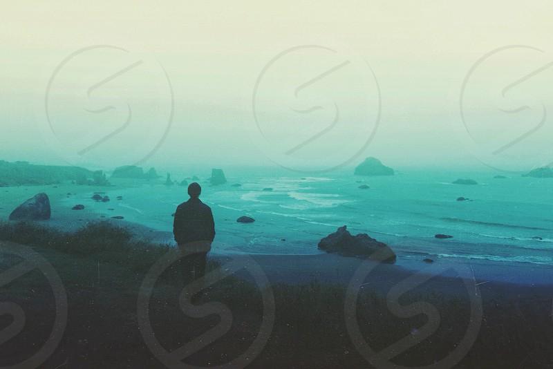 man in black jacket walking on sand photo