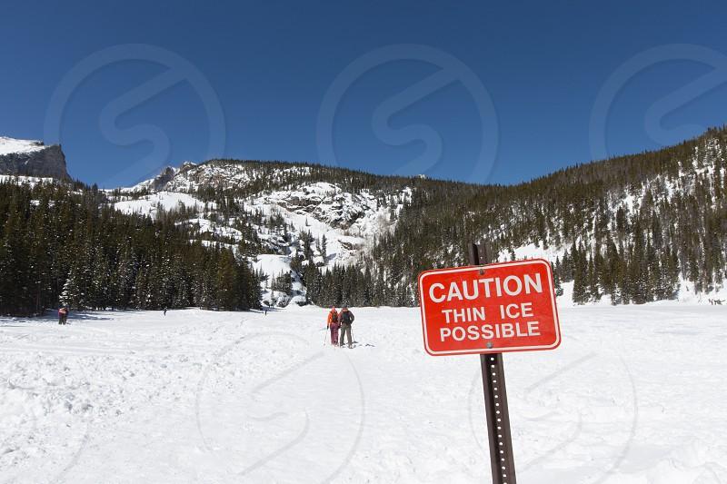 Snowshoers crossing a frozen Bear Lake in Rocky Mountain National Park Colorado. photo