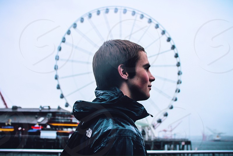 man in black rain coat walking with ferris wheel in background photo