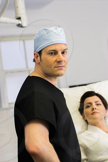 man in black scrub suit wearing white car beside woman in hospital photo