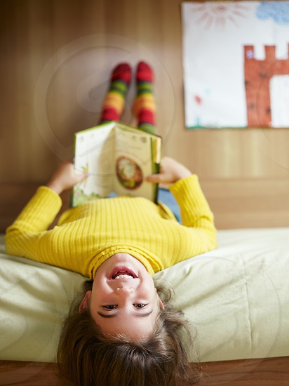 children; girl; reading; book; smiling; happy; bed; one person; portrait; People; kid; kids; girls; only girls; Female; caucasian; 6-7 years; young; pre-teen; pre-teen girl; elementary age; child; childhood; youth; happiness; carefree; joy; fun; cute; looking at camera; full length; holding; lying; laying; lying down; laying down; relaxing; indoor; indoors; home; bedroom; yellow; domestic scenes; everyday scenes; education; tale; imagination; leisure; relaxation; recreation photo