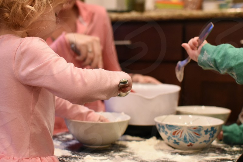 Children helping mix flour for baking photo